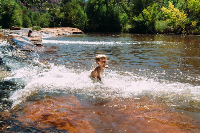 Boy swimming upstream in river
