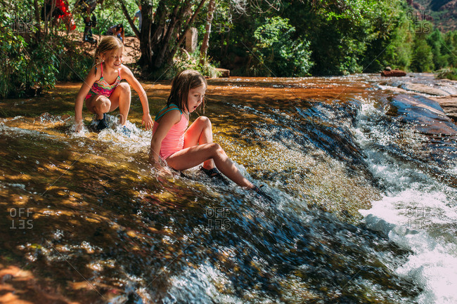 Girls cautiously getting into a river