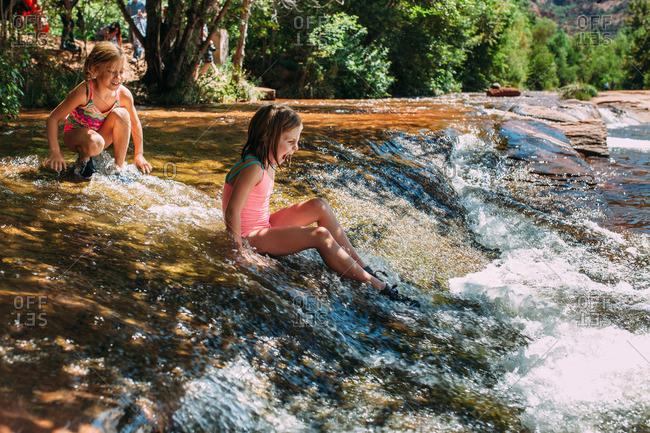 Girls cautiously sliding into a river