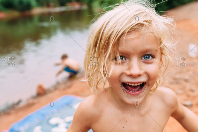 Blonde boy grinning widely on a river bank