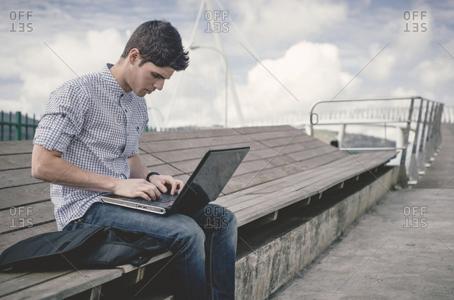 Young man sitting on a bench using laptop