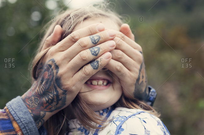 Man's tattooed hands covering eyes of his daughter