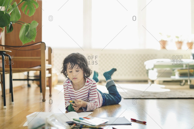 Boy with markers and books lying on floor at home