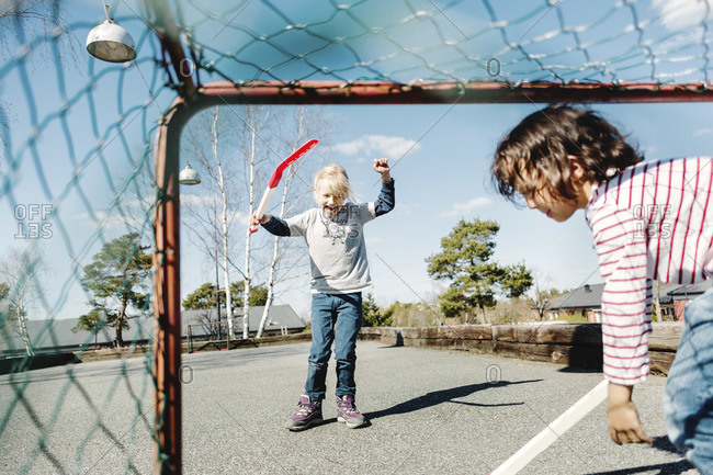 Excited girl gesturing while playing hockey with boy in a yard