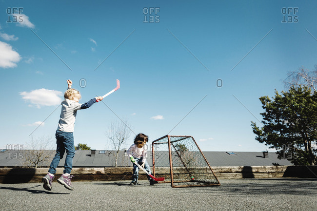 Excited girl playing hockey with boy in a yard against blue sky