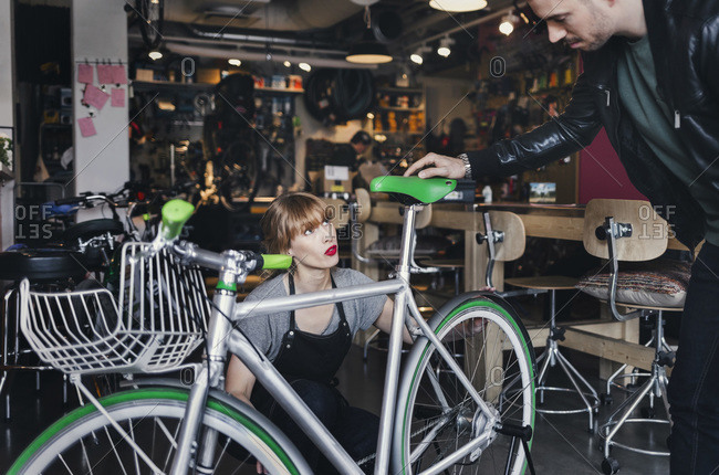 Female mechanic analyzing bicycle while talking to male customer in repair shop
