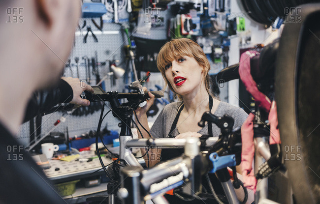 Female mechanic talking to customer in a bicycle repair shop