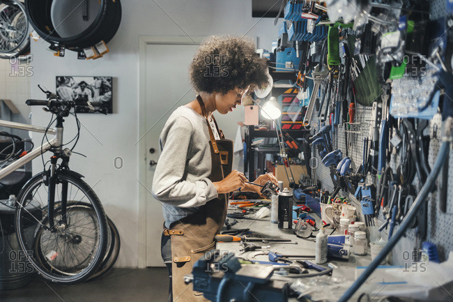 Side view of female mechanic working in a bicycle workshop