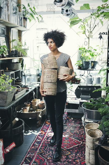 Full length of woman carrying wicker pots in an interior design shop