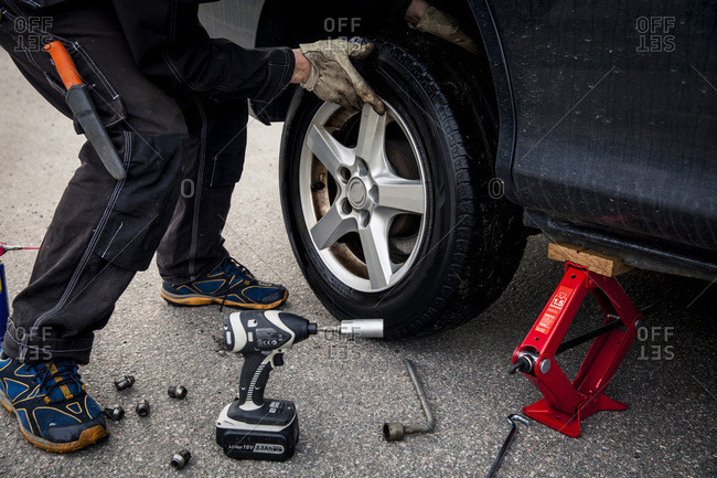 Low section of mechanic changing car tire on street