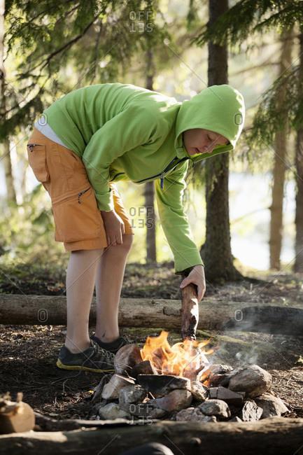Boy igniting campfire at  a lakeshore