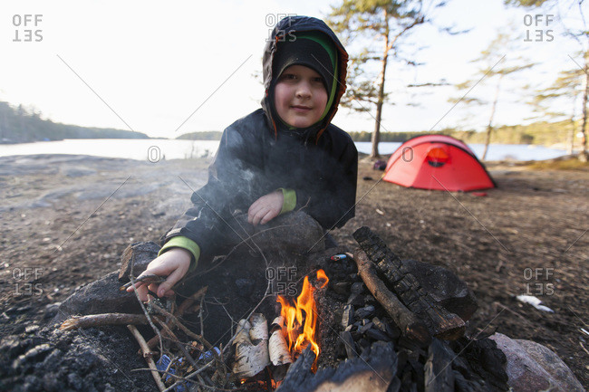 Portrait of smiling boy igniting campfire