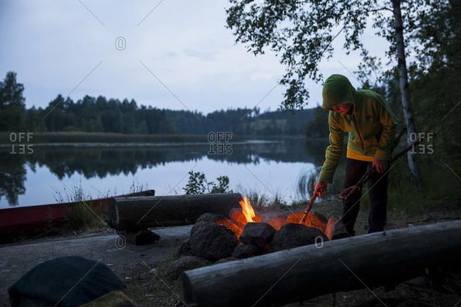 Boy igniting campfire at  a lakeshore during dusk