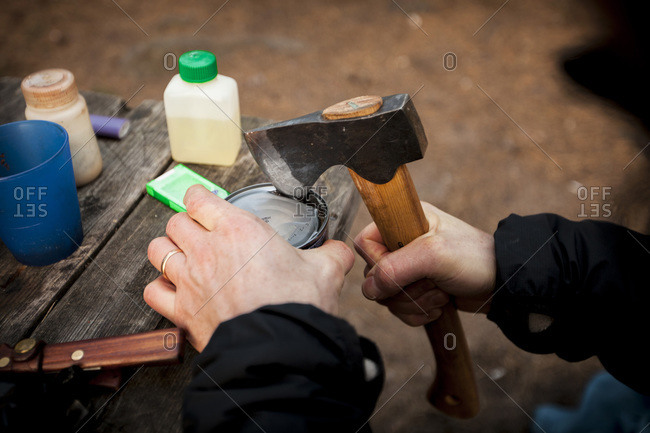 Man's hands opening can with axe at campsite