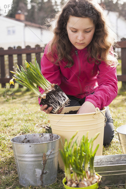 Girl planting flower in a pot in a yard