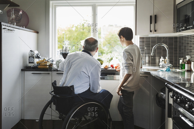 Disabled father preparing food son in a kitchen