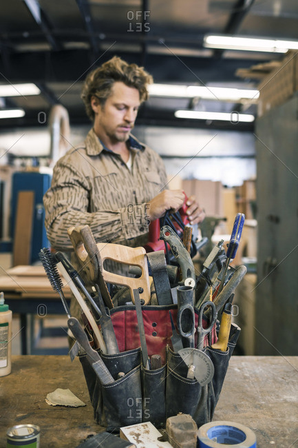Carpenter standing by tool belt on table in a workshop