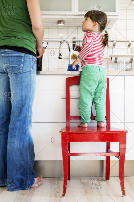 Full length of girl looking at mother while standing on chair in a kitchen