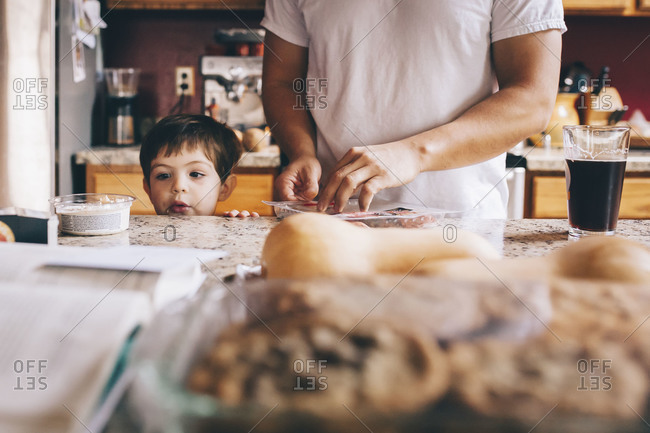 Child peers over counter while man preps Thanksgiving food