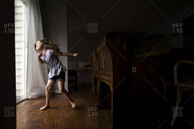 Young girl dancing in dining room