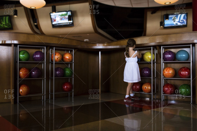 Young girl chooses from colorful balls at a bowling alley