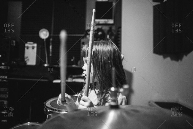 Young girl playing drum kit