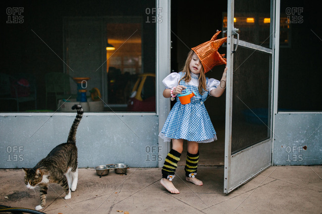 Young girl wearing costume opening door to come outdoors with cat