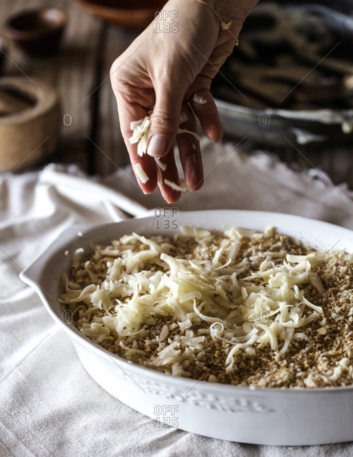 Adding cheese to spicy cauliflower gratin dish before baking