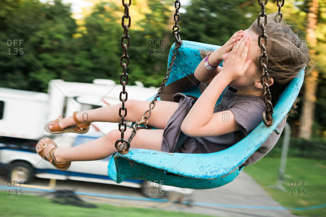 Girl closing her eyes on a swing ride at a fair
