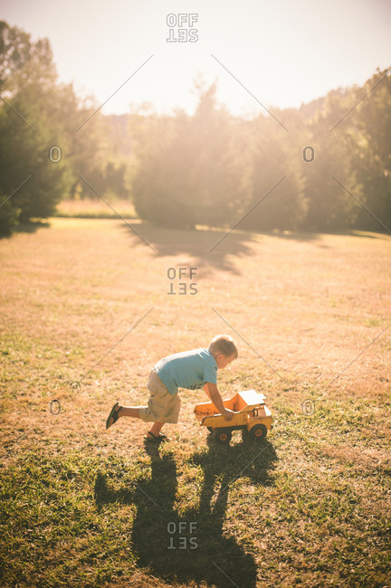 Little boy playing with a toy dump truck in a field