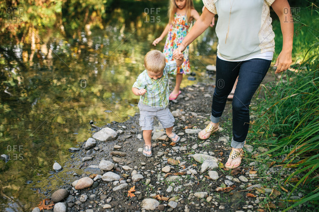 Little boy walking a long a creek's edge with his mother and sister