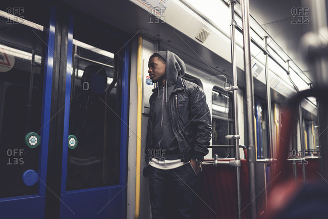 Young man waiting for the doors of a subway car to open