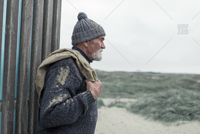 Senior man leaning against a wall looking over a beach