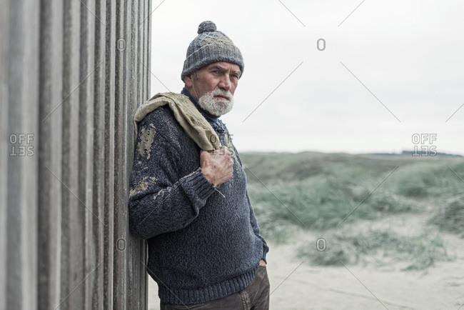 Senior man leaning against a wooden fence at a beach