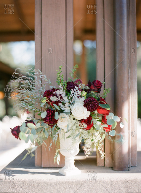 Wedding flower arrangement of white roses and dark red roses and dahlias