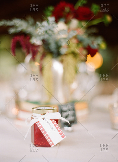 Jar of jam as wedding favor on table with flower arrangement