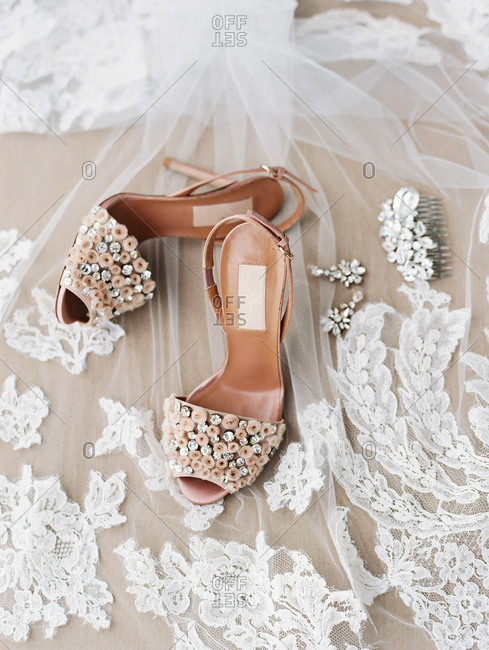 Overhead view of arrangement of shoes and wedding jewelry on veil