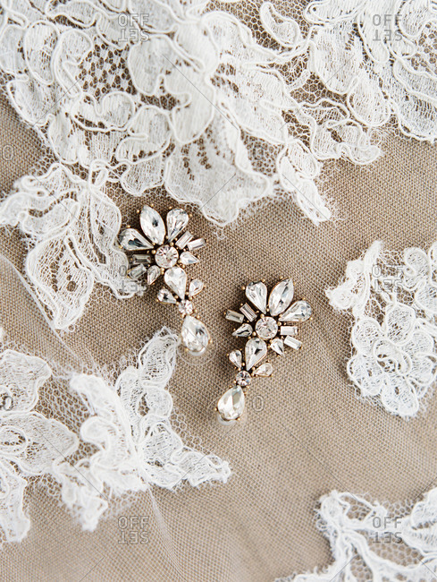 Close-up of vintage style earrings on lace wedding veil