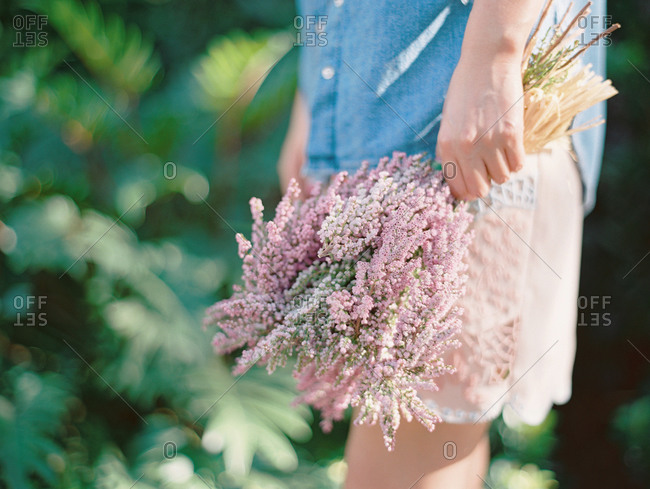 Woman holding a bouquet of pale pink heather flowers