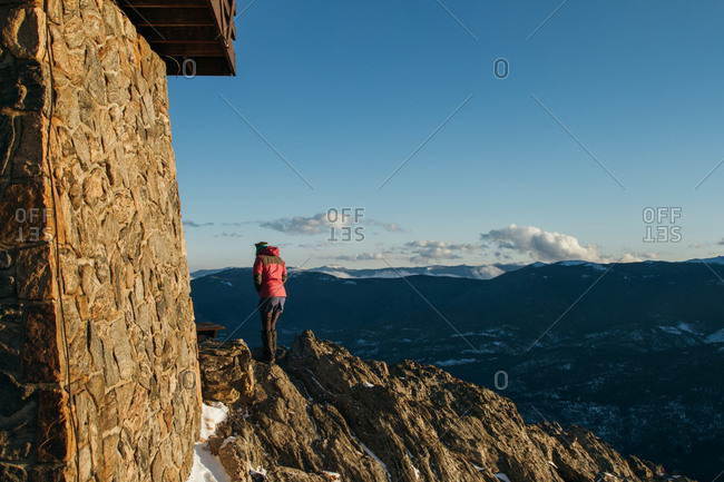 Woman on mountain overlook by building foundation