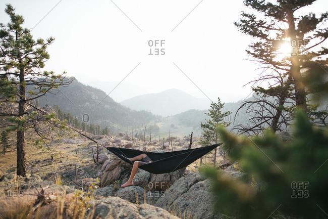 Feet dangling from hammock on mountaintop