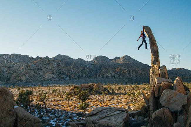 Man dangling from rock tower in desert setting