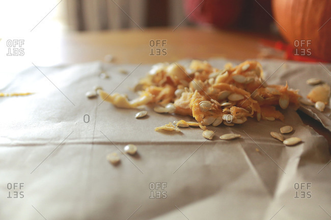 Pumpkin seeds and pulp on paper at table