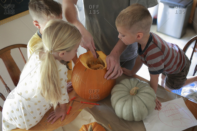 Three children watch as father carves a pumpkin