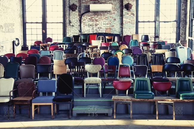 Collection of various vintage chairs on a wooden platform
