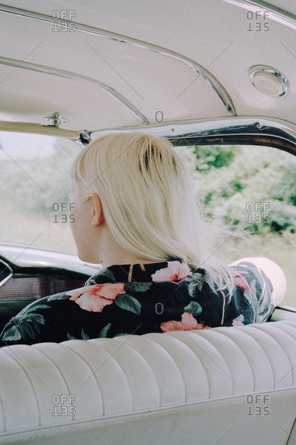 Back view of woman with dyed platinum blond hair in flowered shirt in front seat of classic car