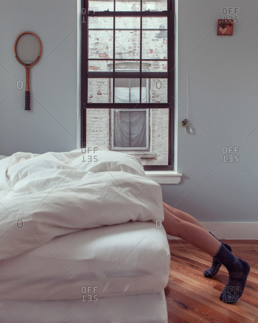 Bedroom with person's legs hanging off bed