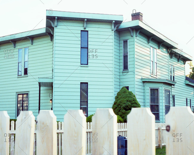 View over fence of Victorian style house with blue siding