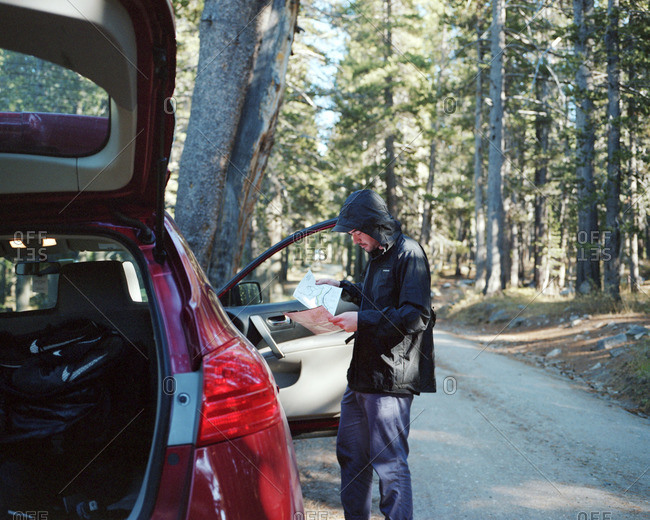 Man in raincoat looking at trail map at car on forest road