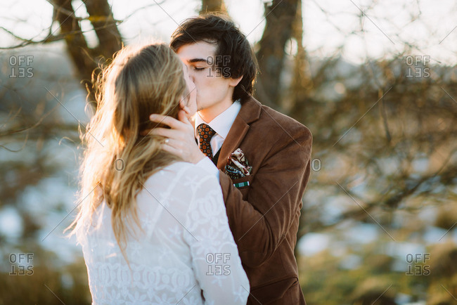 Kissing couple in wedding attire in rural field